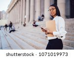 Small photo of Portrait of african american student of faculty of law with folder checking mail on smartphone while looking at camera standing near university building.Dark skinned female lawyer with telephone