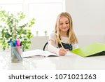 child girl doing homework at... | Shutterstock . vector #1071021263