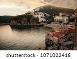 Small photo of old town of Budva on a sunset: ancient walls and a red tiled roof and a view of the bay with the beach, Montenegro, Europe. one of most popular resorts of the Adriatic Riviera.