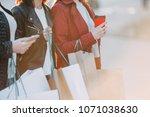 women carrying many shopping... | Shutterstock . vector #1071038630