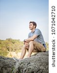 young man hiker sitting on a... | Shutterstock . vector #1071042710