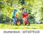children riding balance bike.... | Shutterstock . vector #1071075110