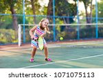 child playing tennis on outdoor ...   Shutterstock . vector #1071075113