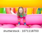 child jumping on colorful... | Shutterstock . vector #1071118703
