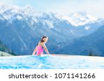 Small photo of Child in outdoor infinity pool with snowy mountain in the background. Family vacation in luxury Alpine resort. Kids in the Alps mountains. Hot tub in snow. Apres ski activity for kids. Children swim.