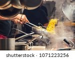 the cook prepares pasta in a... | Shutterstock . vector #1071223256