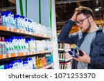 man can't decide in store what... | Shutterstock . vector #1071253370