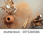A Vase Of Clay And Tools On Th...
