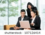 Indian Business colleagues working together around a laptop - stock photo