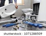 plumber at work in a bathroom ... | Shutterstock . vector #1071288509