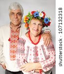 An elderly man hugs a woman. Couple in Ukrainian costumes - stock photo
