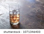 glass of whiskey with ice on...   Shutterstock . vector #1071346403