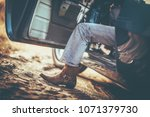 Cowboy and the Classic Muscle Car Taking a Ride. Cowboy Shoes. Leather Boot. - stock photo