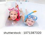 little children in swimsuits... | Shutterstock . vector #1071387320