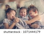 three little girls lying in bed ... | Shutterstock . vector #1071444179