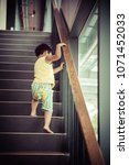 little girl climbing the stairs ... | Shutterstock . vector #1071452033