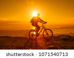 Silhouette Of Cyclist Riding O...