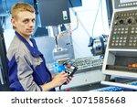 industrial worker operating cnc ... | Shutterstock . vector #1071585668
