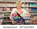 happy female holding basket... | Shutterstock . vector #1071632963