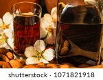 Small photo of Amaretto liqueur, dry almonds and white flowers