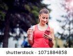 sporty woman using smartphone...   Shutterstock . vector #1071884858