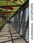 Small photo of the pedestrian overpass is equipped with a modern ramp for disabled people. iron railing elements and colored glass. infrastructure of the provincial Russian city. view of the road and passing cars