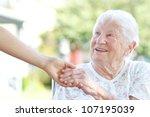 Stock photo happy senior woman holding hands with caretaker 107195039