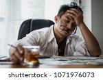 stressed asian businessman... | Shutterstock . vector #1071976073