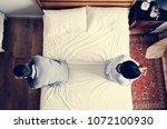 interracial couple sitting back ... | Shutterstock . vector #1072100930