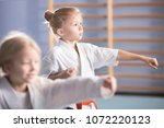 young girl in kimono exercising ... | Shutterstock . vector #1072220123