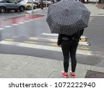 rainy day in the city. woman... | Shutterstock . vector #1072222940
