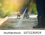 Worker cleaning pathway with high pressure washer splashing the dirt with backlighting,low angle view . High pressure cleaning,lower body with waterproof boots.Professional cleaning services.  - stock photo