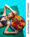 girl in a swimsuit with a plate ... | Shutterstock . vector #1072244600