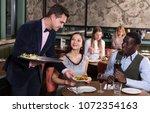 polite elegant waiter bringing... | Shutterstock . vector #1072354163