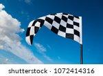checkered flag on blue sky   Shutterstock . vector #1072414316