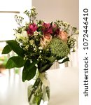 Small photo of Beautiful bridal bouquet sitting in a vintage jar on a white table with aery background