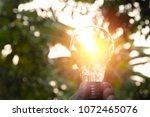 hand holding light bulbs with... | Shutterstock . vector #1072465076