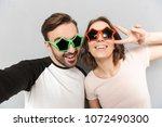 Small photo of Image of amazing couple friends standing isolated over grey wall background make peace gesture wearing sunglasses make selfie.