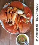 Small photo of Black crab steak cooked to a plate on the wooden table with seafood sauce for a seafood tastes very good.
