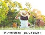 sitting woman near her bike in... | Shutterstock . vector #1072515254