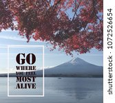 "Small photo of Inspirational motivational quote ""go where you feel most alive"" on Mountain Fuji with autumn leaves background."