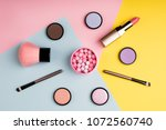 Small photo of Makeup products and decorative cosmetics on color background flat lay. Fashion and beauty blogging concept. Top view