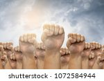 people raised fist air fighting ... | Shutterstock . vector #1072584944