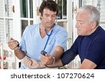 Doctor taking the blood pressure of a patient. - stock photo