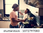 kid feeding mom in the kitchen | Shutterstock . vector #1072797083