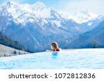 child in outdoor infinity pool... | Shutterstock . vector #1072812836