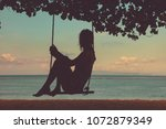 young girl swinging on a sandy... | Shutterstock . vector #1072879349