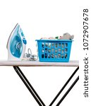Small photo of Electric iron and basket of clean linen on Ironing Board, isolated on white