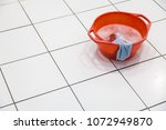 red bowl filled with detergent... | Shutterstock . vector #1072949870