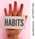 Small photo of Conceptual hand writing showing Habits. Business photo text Regular tendency or practice Routine Usual Manners Behavior Pattern written Cardboard Piece placed the Hand plain background.